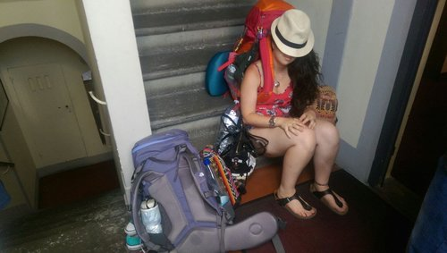 woman asleep with hat over face and bags for travelling