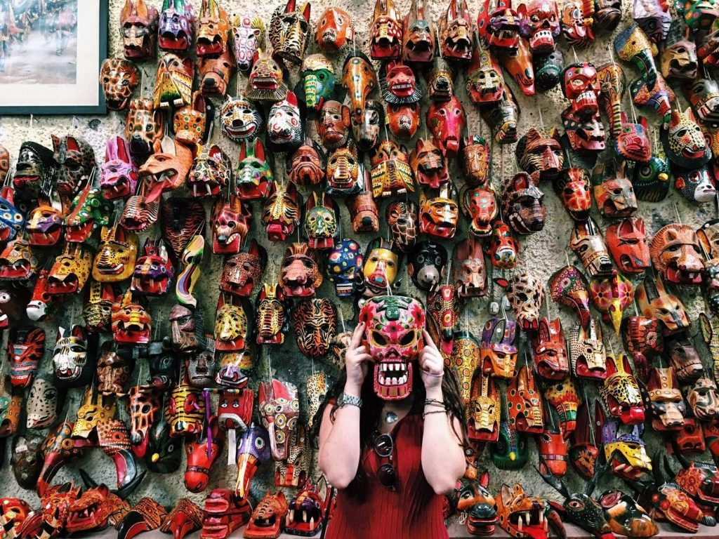 woman in front of wall full of colorful masks