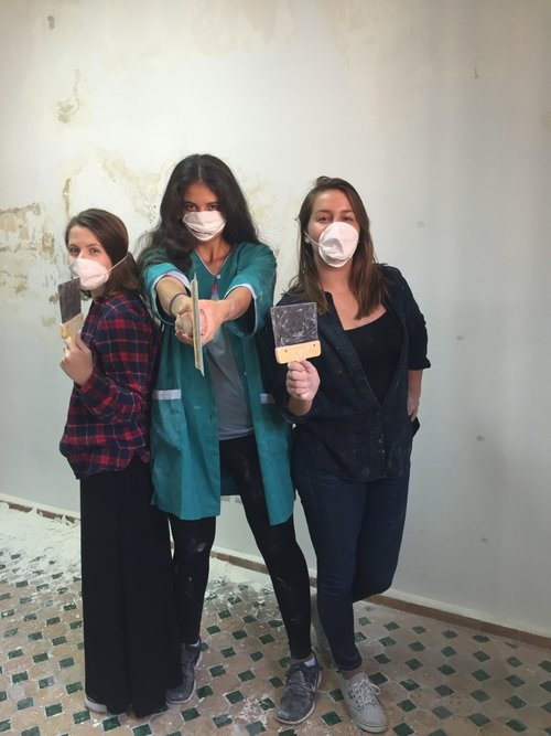 three women posing with tools