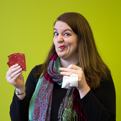 A woman makes a perplexed expression while holding a hand of cards and two tea bags.
